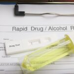 Drug test blank form with test kit and urine,focus on paper