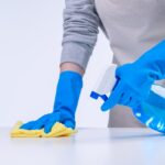 Young woman housekeeper is doing cleaning white table in apron with blue gloves, spray cleaner, wet yellow rag, close up, copy space, blank design concept.
