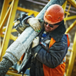 Construction worker carries pipe at worksite